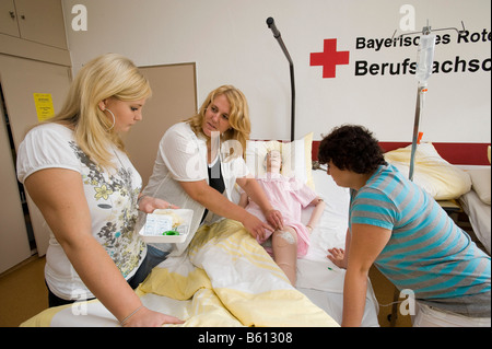 Geriatric care trainer supervising students applying a subcutaneous infusion to a training dummy - Stock Photo