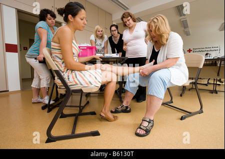 Geriatric care trainer teaching students the correct procedure for applying bandages - Stock Photo