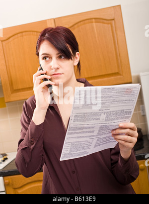 Young adult woman at home querying a large bill using her mobile phone listening and concentrating looking away - Stock Photo