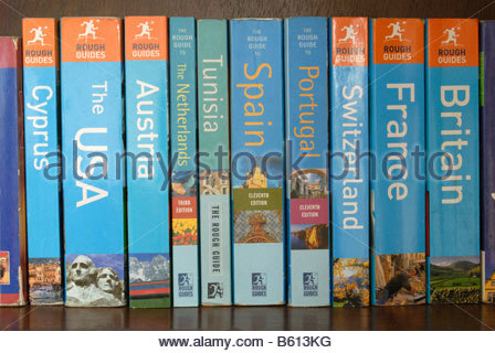 Well-read Rough Guide travel guide books on a bookshelf. - Stock Photo