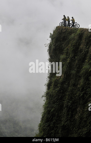 Mountainbikers at the edge of a dangerous cliff, Deathroad, Yungas, La Paz, Bolivia, South America - Stock Photo