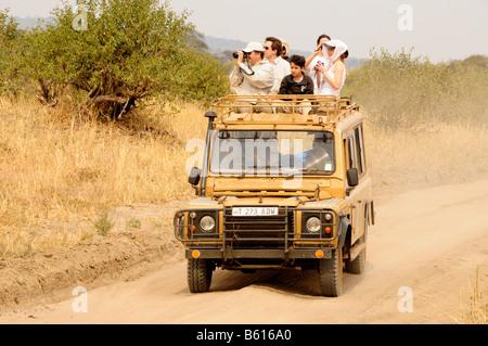 Tourists on safari in a four wheel drive vehicle, Tarangire-National Park, Tanzania, Africa - Stock Photo