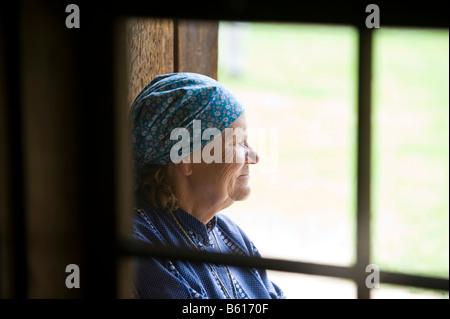 Farmer's wife looking through a window, Open Air Museum, Tallinn, Estonia, Baltic States, Northeastern Europe - Stock Photo