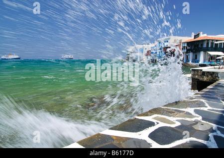 Wave crashing on the promenade along the port of Little Venice, Mykonos Island, Cyclades, Greece, Europe - Stock Photo