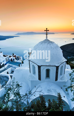 White domed church with a cross at sunset in front of the sea and the volcanic island of Nea Kameni, Santorini, - Stock Photo