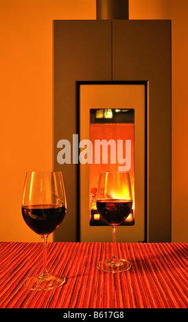 Two glasses of red wine in front of a fire in a fireplace - Stock Photo