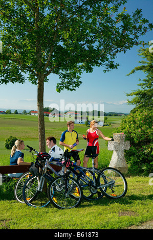 Cyclists having a break at the Plattenberg Mountain, County of Altoetting, Upper Bavaria - Stock Photo