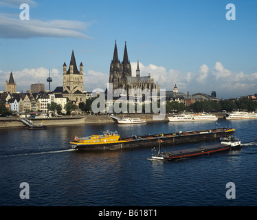 View over the Rhine River to the Cathedral and the Gross St. Martin Church, at front are freight barges and tourists - Stock Photo
