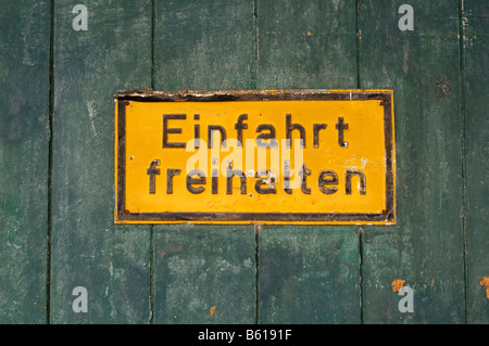 Old yellow sign on a rustical wooden gate: Einfahrt freihalten, Keep the Entrance Clear - Stock Photo