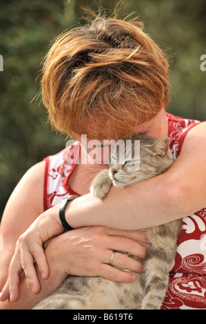 Young grey tabby cat smooching with a woman - Stock Photo