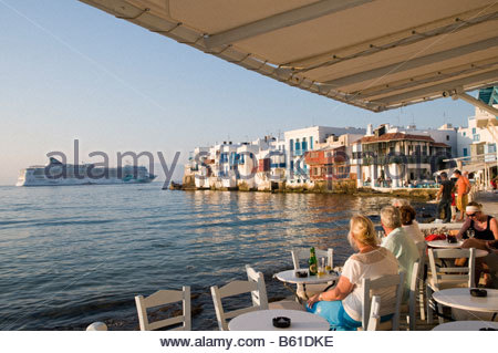 Cruise ship passengers at waterfront restaurant in the Little Venice area of Mykonos Greece - Stock Photo