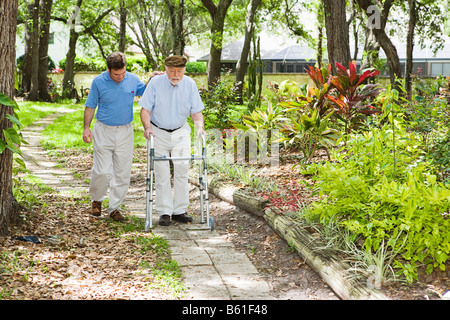 Adult son helping his father use a walker in the park - Stock Photo