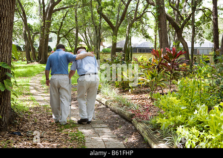 View from behind of an adult son walking with his senior father in the park - Stock Photo