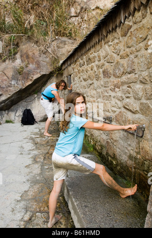 Mother and daughter washing mud from their feet at taps after a mud-flat walk, Normandy, France, Europe - Stock Photo