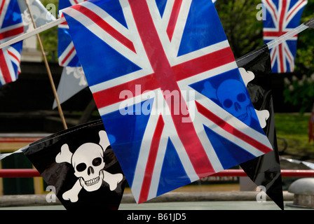 Jolly Roger pirate pennants and Union Jack flags strung up on a narrowboat, Little Venice, London, England - Stock Photo