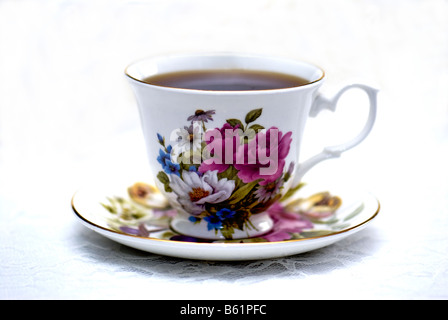 A cup of coffee in a floral cup and saucer, resting on a lace tablecloth. - Stock Photo