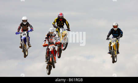 Four jumping motocross riders - Stock Photo