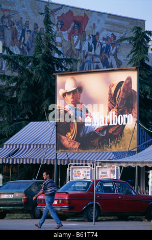 Marlboro cigarette advert billboard, and the National Museum of History (with the Albanian Victorious History mosaic - Stock Photo