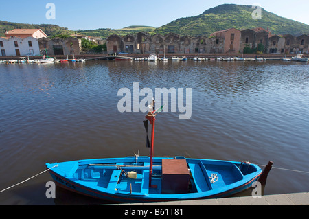 Fishing boat on the Telmo River in Bosa in front of old tanning buildings, Sardinia, Italy, Europe - Stock Photo