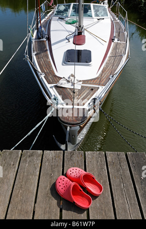 Yacht in the marina in the Achterwasser Bay near Damerow, red bathing shoes, Crocs, Usedom Island, Baltic Sea, Mecklenburg - Stock Photo
