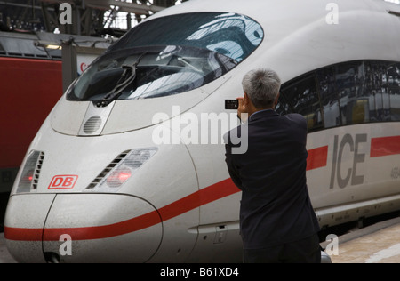 Asian tourist taking a photo of the front of an ICE in Frankfurt main station, Frankfurt am Main, Hesse, Germany, - Stock Photo