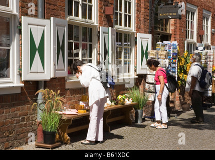 Tourists looking at the special offers in front of a souvenir shop in the dutch quarter of Potsdam, Brandenburg, - Stock Photo