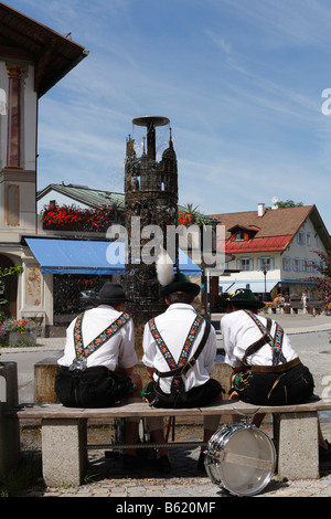 Three young men wearing traditional Lederhosen in front of the fountain on Dorfstrasse, Oberammergau, Upper Bavaria, - Stock Photo