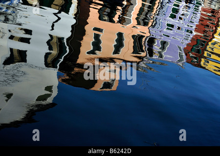 Colourful row houses reflected in water, Burano Island near Venice, Italy, Europe - Stock Photo