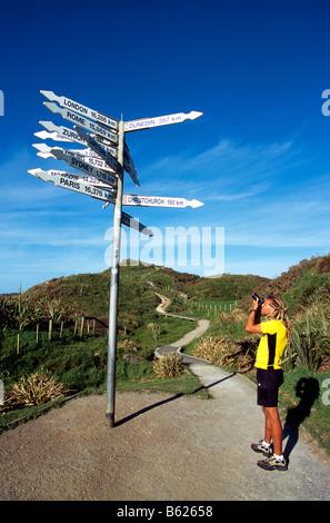 Tourist taking a photo of a direction signpost, Punakaiki, Pancake Rocks, South Island, New Zealand - Stock Photo