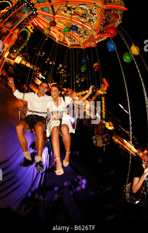 Oktoberfest Beer Festival, Wies'n, couple on the chairoplane, Munich, Bavaria, Germany, Europe - Stock Photo
