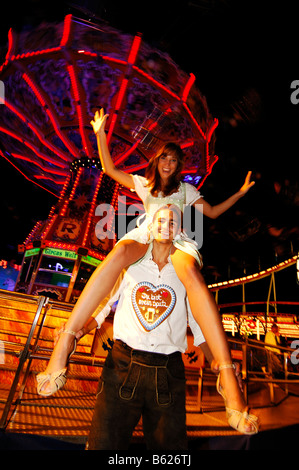 Couple in front of a chain-carousel, Wies'n, Oktoberfest, Munich, Bavaria, Germany, Europe - Stock Photo