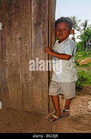 Small, local boy standing in a wooden doorway, Punta Gorda, Belize, Central America - Stock Photo