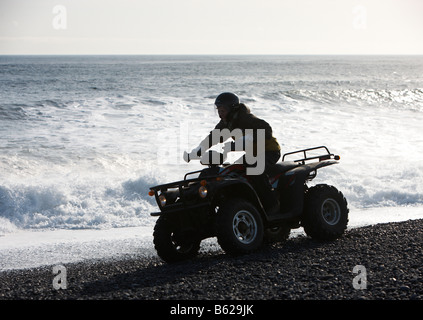 Girl  riding Quad  Bike on black sand rocky beach, Hornafjordur fjord, Eastern Iceland - Stock Photo