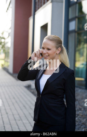 Blonde businesswoman phoning in front of an office building - Stock Photo