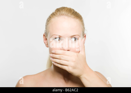 Young blonde woman covering her mouth with her hand - Stock Photo