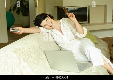 Woman with a laptop on a sofa, web surfing, online dating, Internet purchases - Stock Photo