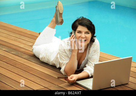 Woman reclined beside a swimming pool with a laptop in front of her, web surfing, online dating, Internet purchases - Stock Photo