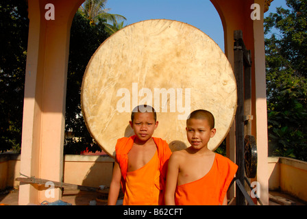 Buddhist novice monks standing in front of a large, round drum, Wat Phonxay, Vientiane, Laos, Southeast Asia - Stock Photo