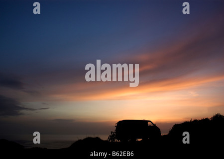 A camper van and two bikes silhouetted against the sunset - Stock Photo
