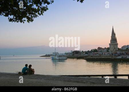 Couple sitting at the harbour entrance at dusk opposite the old prison tower La Rochelle Charente Maritime France - Stock Photo