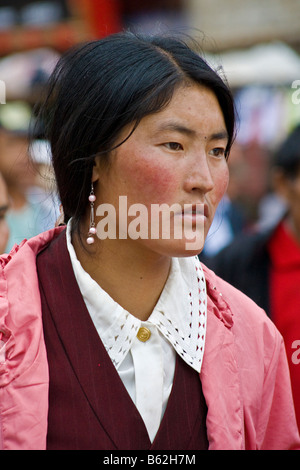 Beautiful young Tibetan woman pilgrim wearing earrings in the Barkhor, Lhasa, Tibet. JMH3708 - Stock Photo