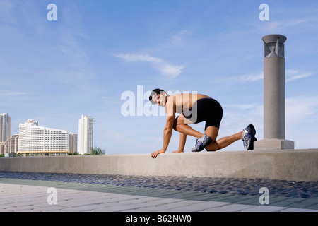 Young man preparing for running on the ledge - Stock Photo