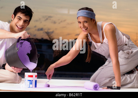 Young couple mixing colors and smiling - Stock Photo
