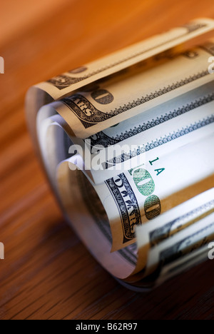 Close-up of a roll of one hundred dollar bills - Stock Photo
