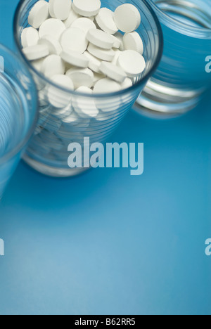 Close-up of a glass full of pills with two glasses of water - Stock Photo