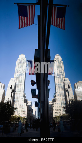 Low angle view of American flags hanging on poles with skyscrapers in the background, New York City, New York State, - Stock Photo