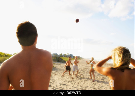 Five friends playing American football on the beach - Stock Photo