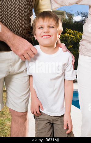 Boy standing with his parents at the poolside - Stock Photo