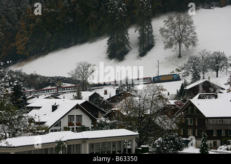 Electric Train in snow leaving Giswil, Switzerland towards the Brunig pass. - Stock Photo