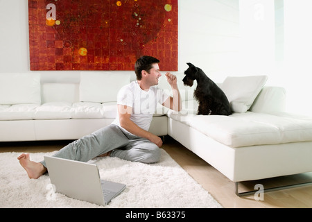 Mid adult man sitting on rug and playing with dog - Stock Photo